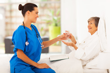 caring young caregiver bring a glass of water to senior woman