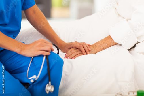 medical doctor holing senior patient's hands and comforting her
