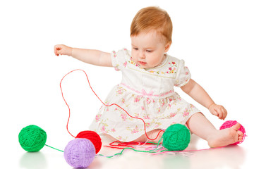 Little girl with colored balls of yarn