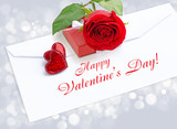 Two decorative hearts with a red rose and box by a gift on a pos