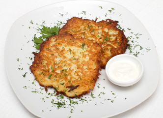 Fried potato pancake with sauce on a plate