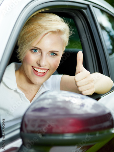 Beautiful 20s driving a red car and shows thumb up