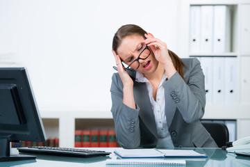 geschäftsfrau mit kopfschmerzen am arbeitsplatz