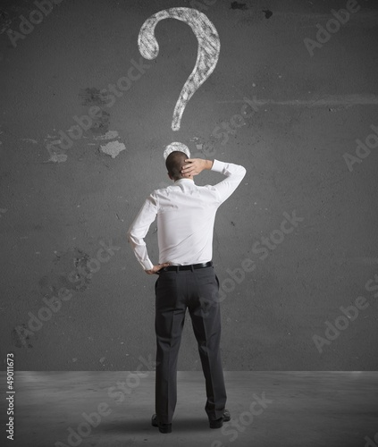 Confused businessman looking at question mark