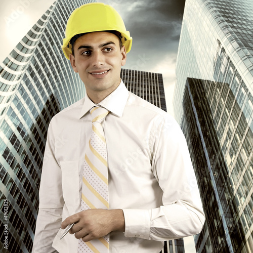 Young architect wearing a protective helmet standing on the buil
