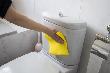 A woman cleans a toilet with yellow cloth
