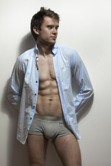 Sexy male fitness model in brief shorts and blue shirt