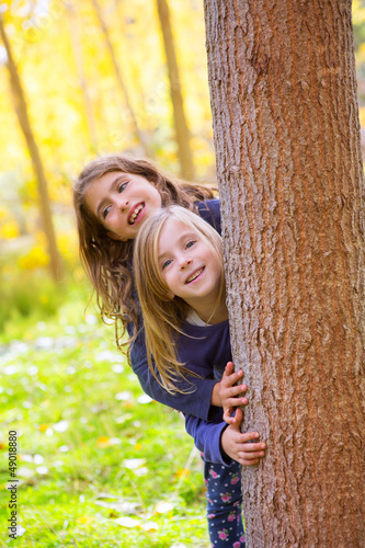 Autumn sister kid girls playing in forest trunk outdoor