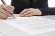 Business woman signing a contract above signature line