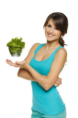Light food concept. Smiling woman balancing lettuce