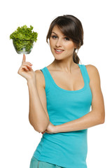 Light food concept. Woman balancing bowl with salad on finger