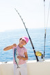 child little girl fishing in boat holding little tunny fish catc