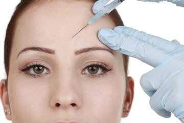 Frau bekommt Spritze gegen Falten in die Stirn