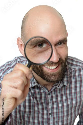 Lachender Mann mit Lupe