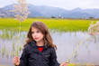 Brunette kid girl outdoor holding spike in wetlands lake