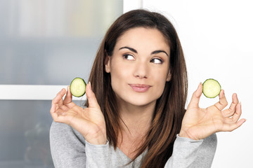 Woman with a slice of cucumber