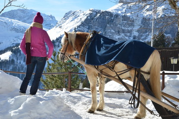 Girl and a horse against Alpine panorama