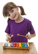 little girl playing xylophone - isolated on a white background