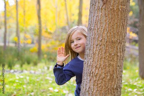 Autumn forest with child girl greeting hand in tree trunk