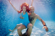 Father and daughter having fun underwater in swimming pool.