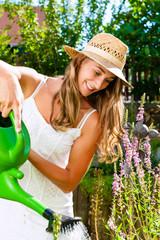Woman gardener watering flowers in garden