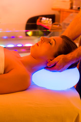 Woman enjoying therapy in spa with color therapy