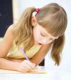 Little girl is writing using a pen