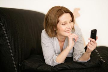 Frau mit Smartphone auf der Couch