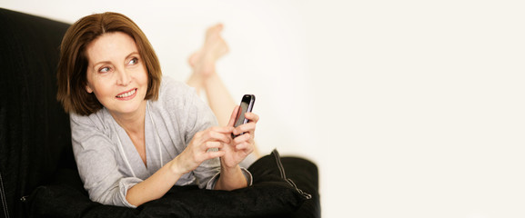 Frau zuhause mit Handy