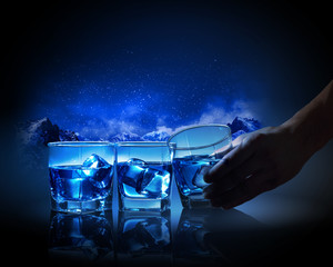 Three glasses of blue liquid with ice