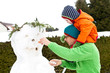 Vater und Sohn bauen einen Schneemann