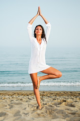 Pretty woman doing yoga on the beach