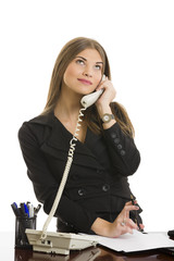 Pretty businesswoman looking up and speaking on phone at office.