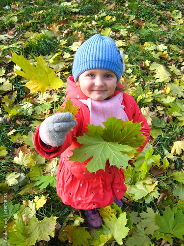 The little girl with yellow leaf in autumn