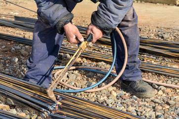 Welder cutting steel bars