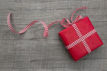 Ein rotes Weihnachtsgeschenk isoliert mit Holz