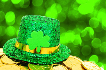 St Patricks Day hat and gold coins on green background