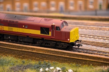 Red and yellow weathered model train diesel engine