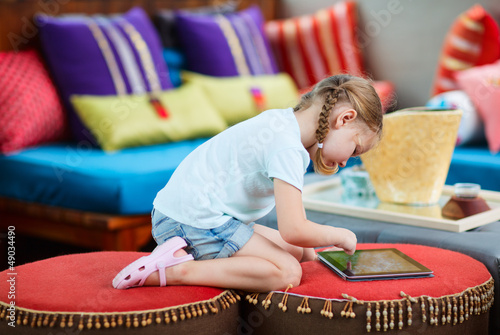 Little girl playing on tablet device