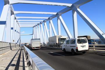ゲートブリッジを走行する車とトラック