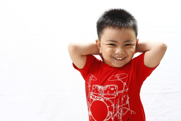 Little Boy Smiling while Holding Back of Head