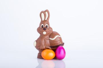 Osterhase aus Schokolade mit Ostereiern vor weißem Hintergrund