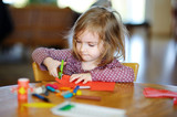 Little preschooler girl cutting paper