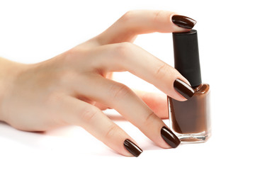Hand with brown manicure and nail polish bottle isolated