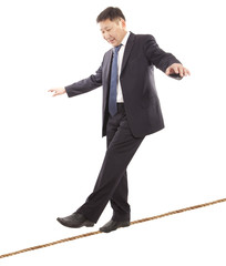Asian businessman rope-walker