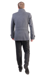 Back view of going  handsome business man in coat