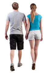 Back view of going young couple (man and woman)