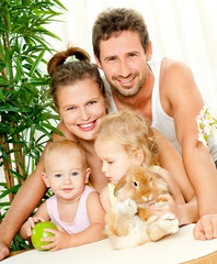 Young happy family with a pet rabbit