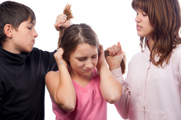 Teenagers pulling hair of smaller teenage girl