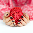Cupped hands with dark manicure holding decoration ball closeup